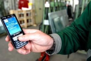 Mitarbeiter-von-Glas-Fillinger-bei-der-Arbeitszeitbuchung-im-Handy_Grossaufnahme-1024x685